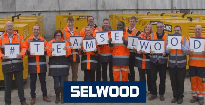 Selwood team in orange high vis jackets and hard hats holding a sign saying Team Selwood